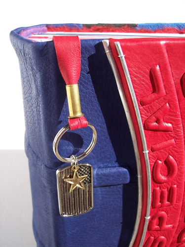 American flag keychain with star pendant on red leather lace as bookmark on military photo album