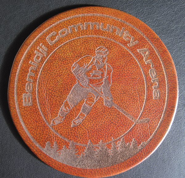 Sports hockey logo laser engraved into round leather disk on hockey arena book