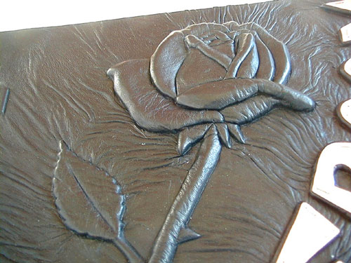 handcarved rose sculpture embossed under black leather on photo album book cover
