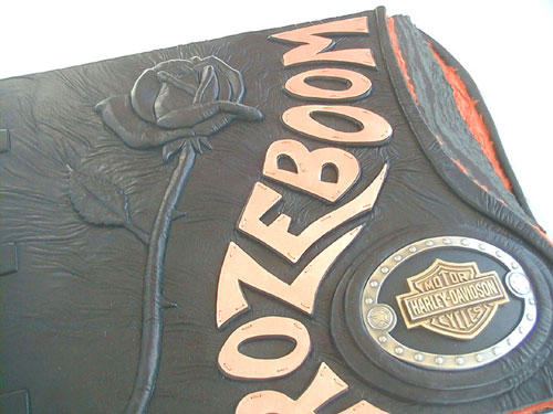 rose sculpture embossed under black leather with copper name Rozeboom and motorcycle belt buckle on book cover