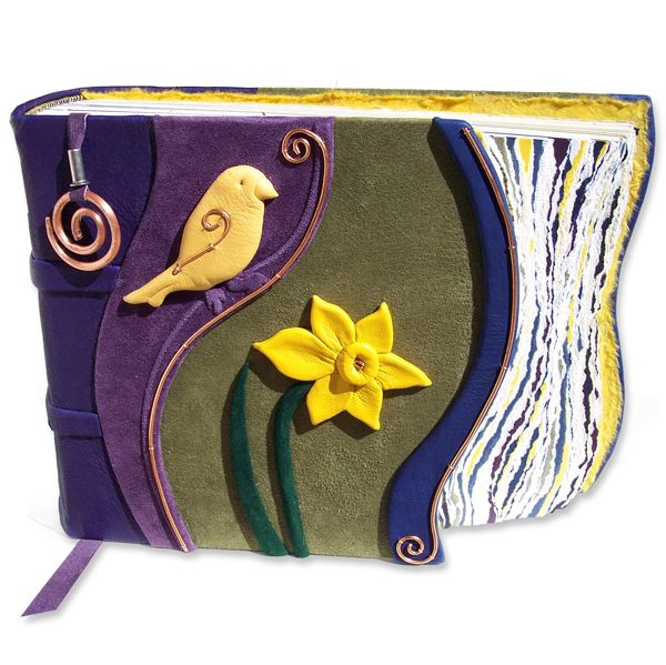 handcarved yellow leather chickadee and daffodil on green, purple, and blue leather photo album with copper spiral bookmark