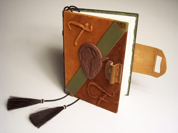 leather closure flap and pen holder on journal