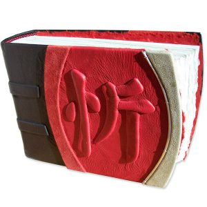 Chinese kanji character JOY embossed under red leather on handbound scrapbook album