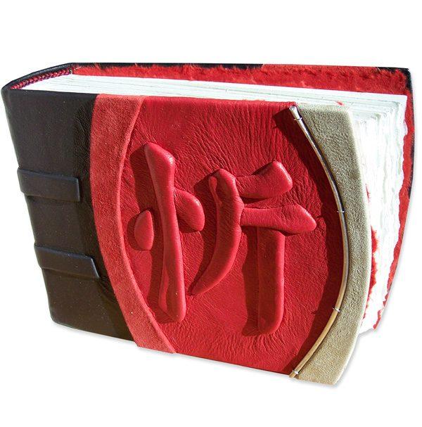 Chinese kanji character JOY embossed under red leather on handbound scrapbook album