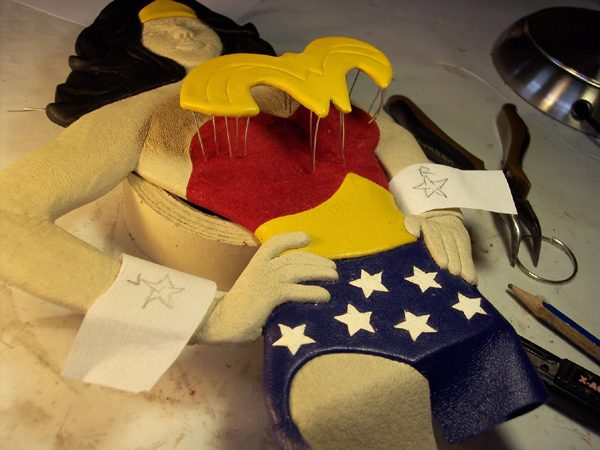 yellow leather Wonder Woman logo on sculpted figure for book cover