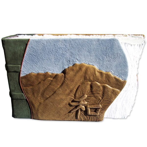 handvcarved mountain landscape embossed under brown lather on book cover with suede blue sky and chinese character for Harmony