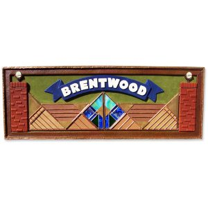 framed leather wall hanging with name Brentwood on blue banner over stained glass and copper gate