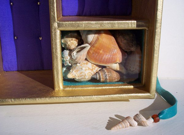 Interior of metallic gold leather box with shells under glass window