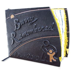 Custom leather Doctor Retirement scrapbook with embossed lettering, dates, Children;s Hospital logo with copper child