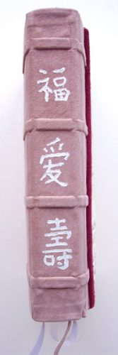 hand painted chinese characters on pink suede Bible spine stating Luck, Love, and Longevity