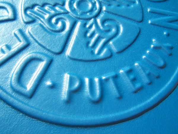 Car logo De Dion Bouton Puteaux embossed under turquoise automotive upholstery leather on book cover