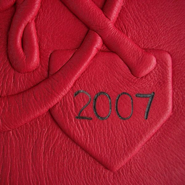 red leather baseball home plate closeup on leather book with branded date