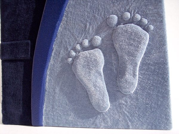 baby footprints embossed under blue suede leather on book cover