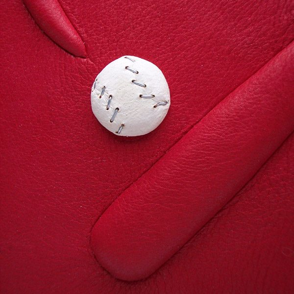 miniature white leather base ball with silver threads on red leatherbound photo album