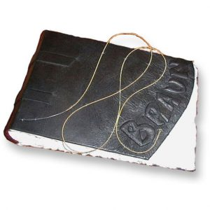 Guitar string looped on cover of custom black leather scrapbook with embossed name Braun