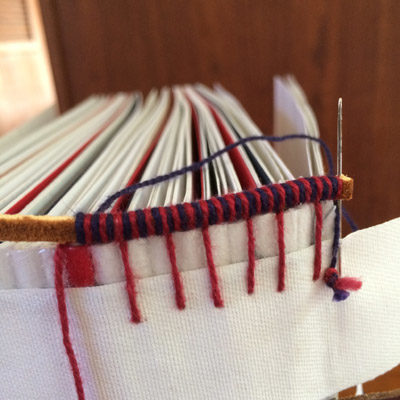 Handsewing leather book headbands onto spine of scrapbook with red and blue threads