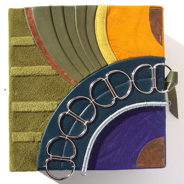 colorful green, gold, teal, and purple clamshell box lid with D rings in an arch