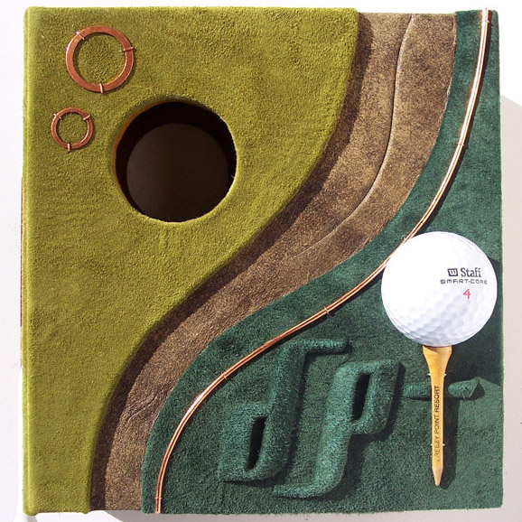 leather clamshell box with golf ball, golf tee, sandtrap, initials, hole in one box