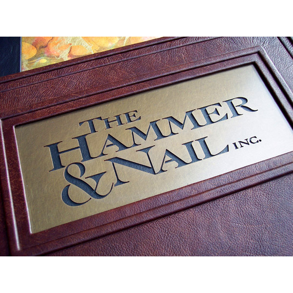 The Hammer and Nail company logo waterjet etched into brass plate on leather book cover