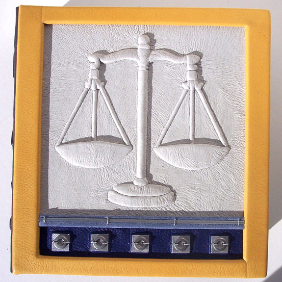 front cover of leather box for judge, scales of justice embossed under white leather with yellow leather frame