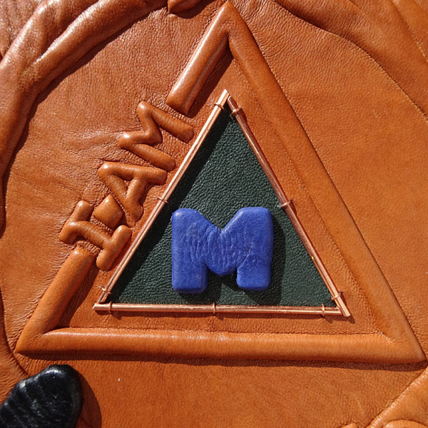 I AM leather embossed triangle with blue M logo on custom leather book cover