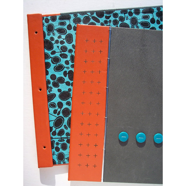 branded orange leather spine on custom leather artist portfolio book with turquoise dots