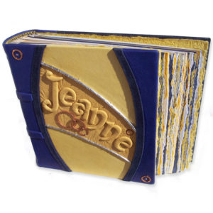 yellow and blue leather photo album with embossed name and copper