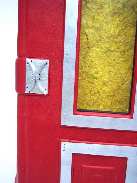 Silver door hinge hardware on red leather door photo album