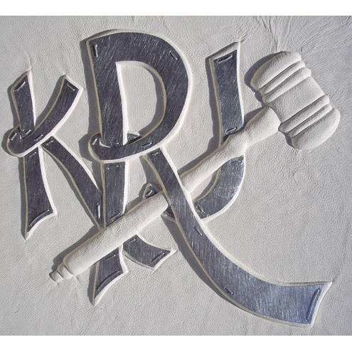 silver capped monogram embossed under white leather with judicial gavel