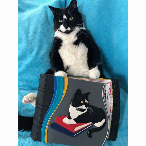 Black and White Tuxedo Cat posing with Custom Leather Scrapbook Album of his likeness