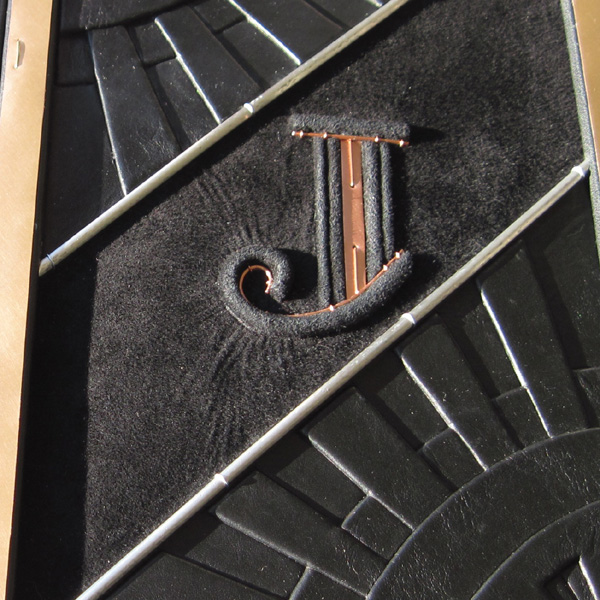 Copper initial J embossed raised from surface on custom black leather art deco wedding album cover
