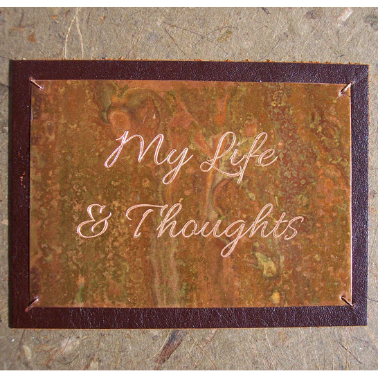 Engraved copper plate on book cover with My Life and Thoughts etched lettering over a leather frame