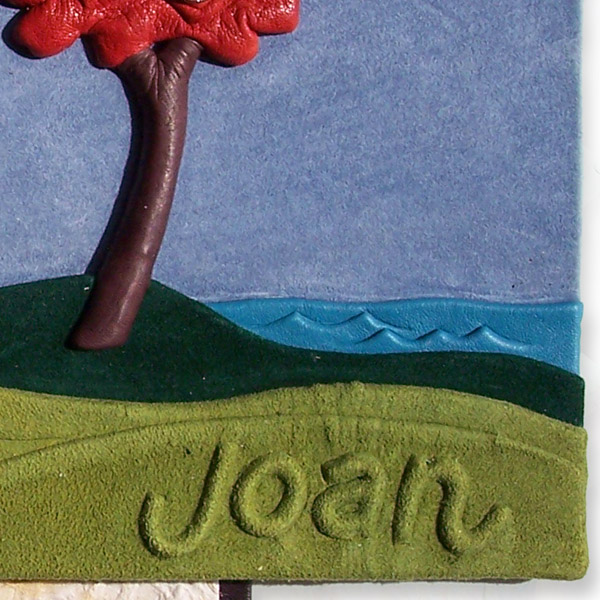 embossed name Joan on leather landscape with red tree and lake