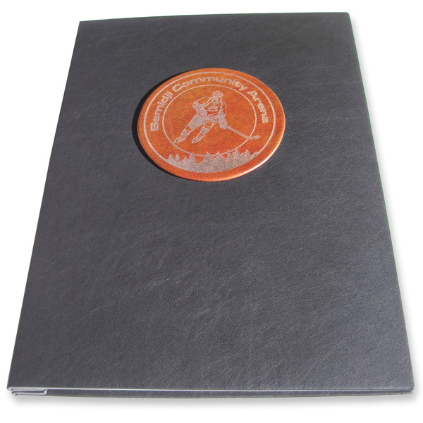 Laser engraved Branded hockey logo on round brown leather disk on book cover