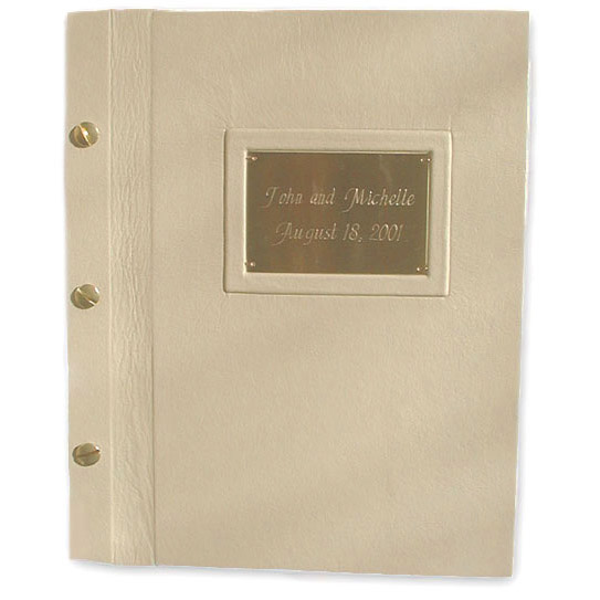 framed etched metal name plate on beige leather book cover bound with brass screwposts as wedding album