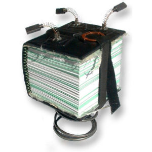 small thick handbound book mounted on a spring with 3 brush springs on the top cover, black leather with lace closure