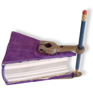 triangle shaped handbound purple leather book with a steel truck part holding a pencil