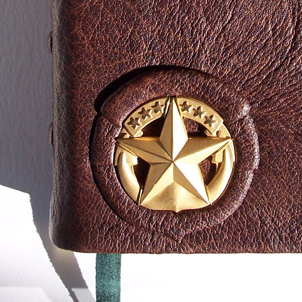 Gold star emblem on brown leather military Bible, inset bronze star crest