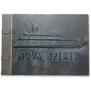 embossed black leather guestbook for superyacht Nova Spirit with carved boat image and yacht name