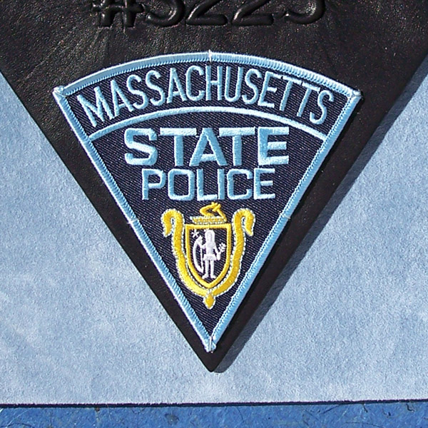 Massachusetts State Police trooper patch mounted to blue suede leather book cover