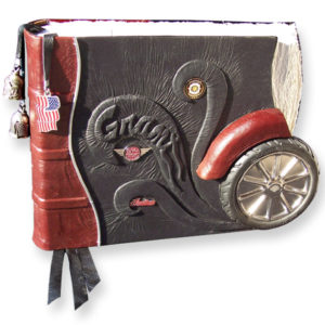 Motorcycle leather scrapbook with tire ashtray as cycle wheel, Indian pins, bells as pagemarkers, enbossed name Grant behind bike