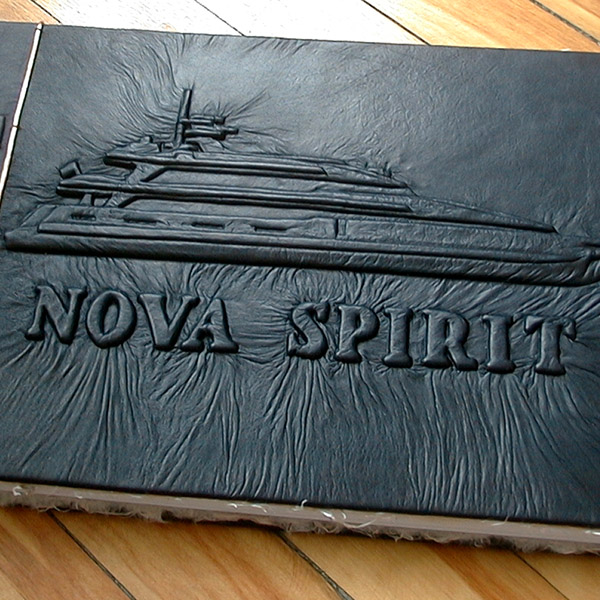 Nova Spirit Super yacht name embossed under black leather with carved boat as yacht guestbook