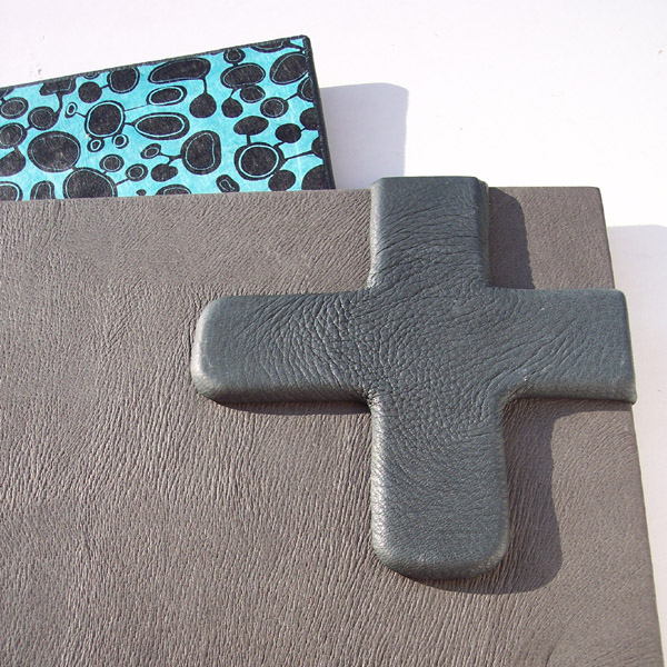 + Plus symbol wrapped in gray leather on portfolio book cover