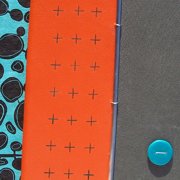 branded + Plus symbol on orange leather book cover with turquoise dot