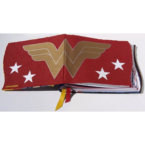 Wonder Woman logo in gold on red handmade paper coversheets in scrapbook with stars
