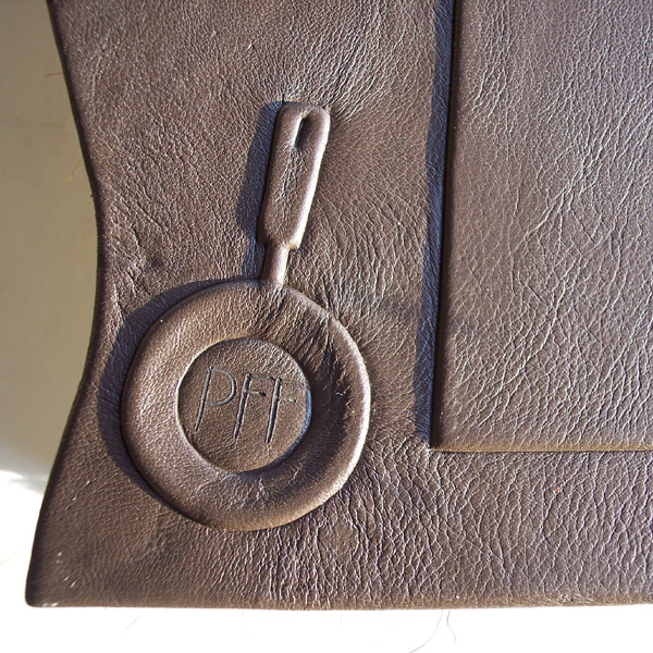 frying pan embossed under brown leather with branded initials on back of book cover