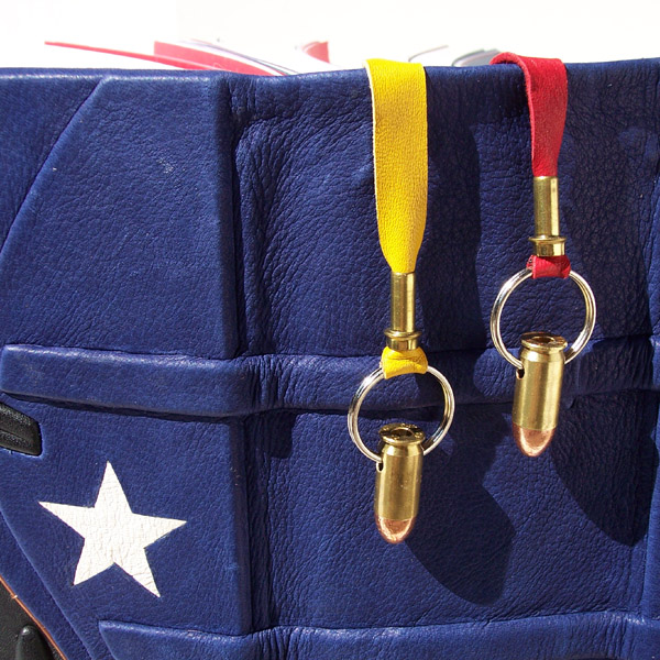 wonder woman bullet pendants as bookmarks on leather scrapbook with white star