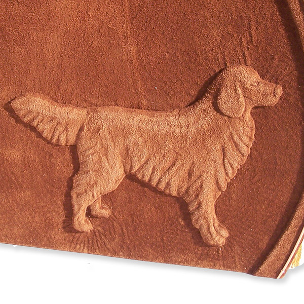 golden retriever artwork embossed under brown leather on book cover, hand carved dog sculpture