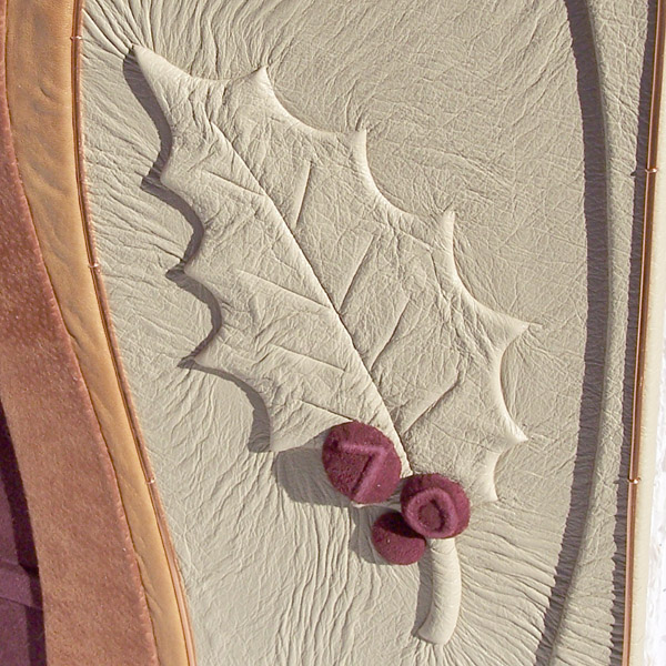 Holly leaf embossed under leather with 70 on red holly berries for 70th birthday