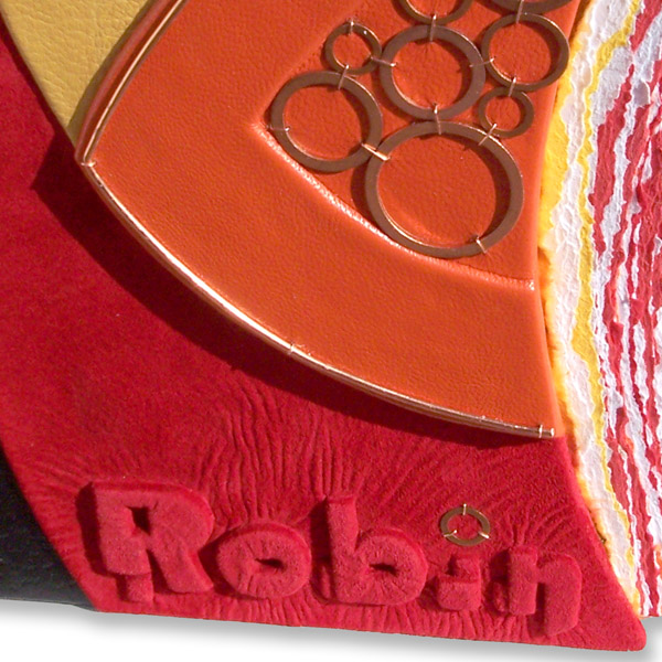 name Robin embossed under red suede leather on book cover with copper washers on orange curved cover edge